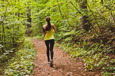 woman jogging through wooded path